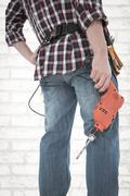 Composite image of male handyman holding drill machine Stock Photos