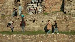 Young boys and girls tourists climbing up on remains of the old ruined tower. Stock Footage