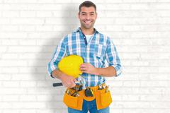 Composite image of smiling handyman holding hardhat and hammer Stock Photos