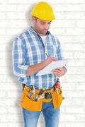 Stock Photo of Composite image of manual worker writing on clipboard
