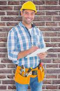 Composite image of portrait of smiling handyman writing on clipboard Stock Photos