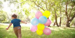 Smiling boy running in park with balloons slow motion Stock Footage