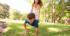 Mother and happy son playing wheelbarrow in sunny park Stock Footage