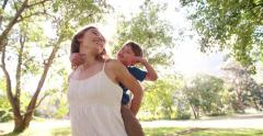 Boy piggybacking on his mother's back in a sunny park Stock Footage