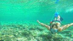 UNDERWATER SLOW MOTION: Female diver exploring the coral reef Stock Footage