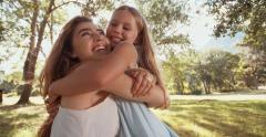 Happy girl and her mom sharing a loving hug outdoors - stock footage