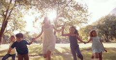 Mother holding hands with kids running through park - stock footage