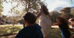 Parent running with kids through a sunlit park - stock footage