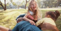Children climbing and tickling father lying in grass in park Stock Footage