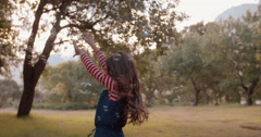 Little girl filled with wonder playing with bubbles in field Stock Footage