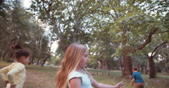 Friendly little kids running and chasing bubbles in a park - stock footage