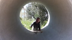 Baby gets in to concrete pipe - stock footage
