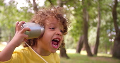 Little boy listening to sound through a tin can phone Stock Footage
