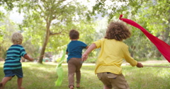 Children playing and running in a park with colorful banners - stock footage