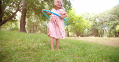 Girl trying to hula hoop in park Stock Footage
