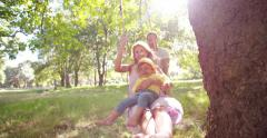Dad pushing mom and little girl on a swing - stock footage