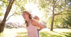 Laughing mom piggybacking her little toddler girl in a park Stock Footage
