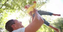 Happy father lifting his laughing little girl playfully Stock Footage