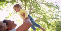 Laughing parents playing with their little girl in the park - stock footage