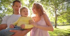 Family with toddler smiling at bubbles in a park Stock Footage