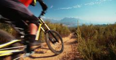 High angle view of mountain biker riding a dirt path downhill - stock footage