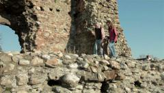 Grandfather with two young granddaughter walking on remains of old ancient town. Stock Footage