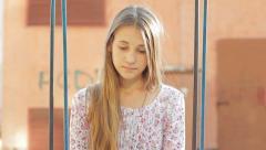 Stock Video Footage of Sad Pretty Teen Girl Sitting on Swing HD