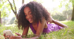 Smiling Afro girl in the park on the phone Stock Footage
