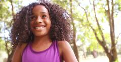 Happy Afro girl smiling innocently in a sunlit park Stock Footage
