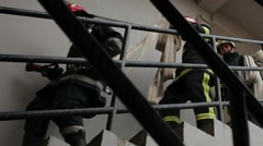 Firefighters in ull gear climbing down stairwell Stock Footage