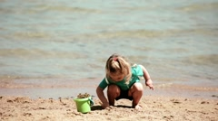 Baby girl playing dig on the beach of sand sea with a bucket and shovel scoop Stock Footage