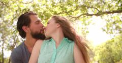 Romantic couple kissing and hugging in a park Stock Footage