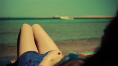 Young pure girl woman lying on beach sea, wears sunglasses. Golden color grading Stock Footage