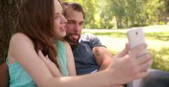 Couple pulling faces for a selfie with their phone Stock Footage