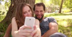 Smiling couple taking selfie on their phone in a park Stock Footage