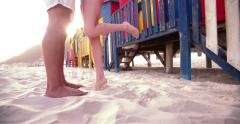 Couple's legs facing each other in the sand on beach Stock Footage