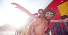 Cute guy piggybacking his girlfriend in front of beach huts Stock Footage