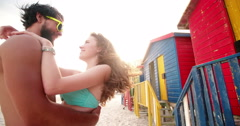 Couple standing in front of beach huts Stock Footage