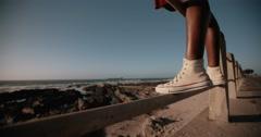 Teenager wearing sneaker standing at seaside Stock Footage