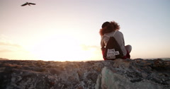 Pensive Afro hipster teen sitting quietly by herself on a beach at sunset - stock footage