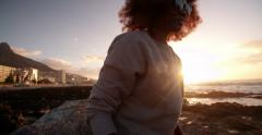 Afro teen hipster at the beach with sun flare - stock footage