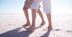 Close-up of senior couple's legs and feet walking in the sand Stock Footage