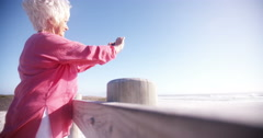 Retired senior woman taking picture of beach on phone Stock Footage
