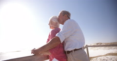 Affectionate elderly retired couple enjoying time at the beach Stock Footage