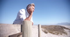 Active retired senior on the phone at the beach Stock Footage