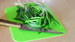 Green onions on a green cutting board, cutting rings in the kitchen Stock Footage