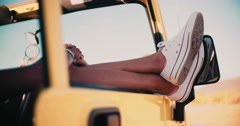 Legs and feet sticking out of car window on road trip Stock Footage