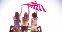 Multi ethnic group of girls happily flying an American flag - stock footage