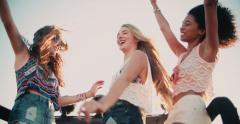 Girl friends dancing in vehicle at beach on road trip Stock Footage