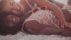 Afro girl and her friend laughing and joking on beach - stock footage